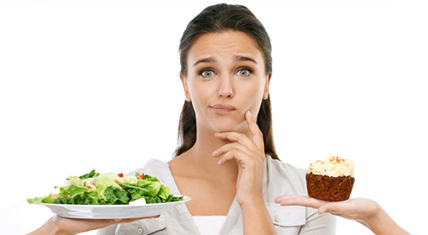 Studio shot of a young woman choosing between a healthy and unhealthy diet