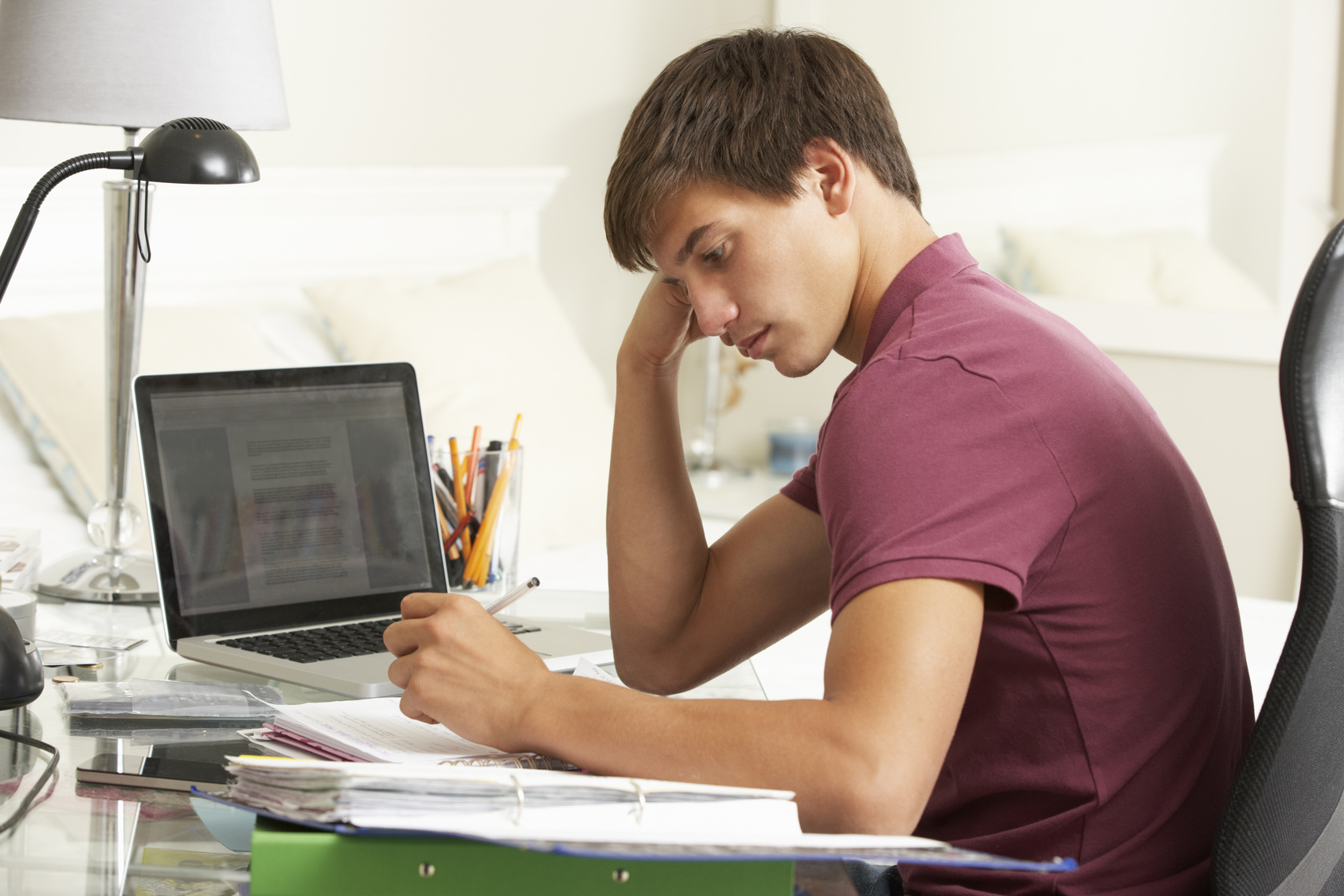 Teenage Boy Studying At Desk In Bedroom
