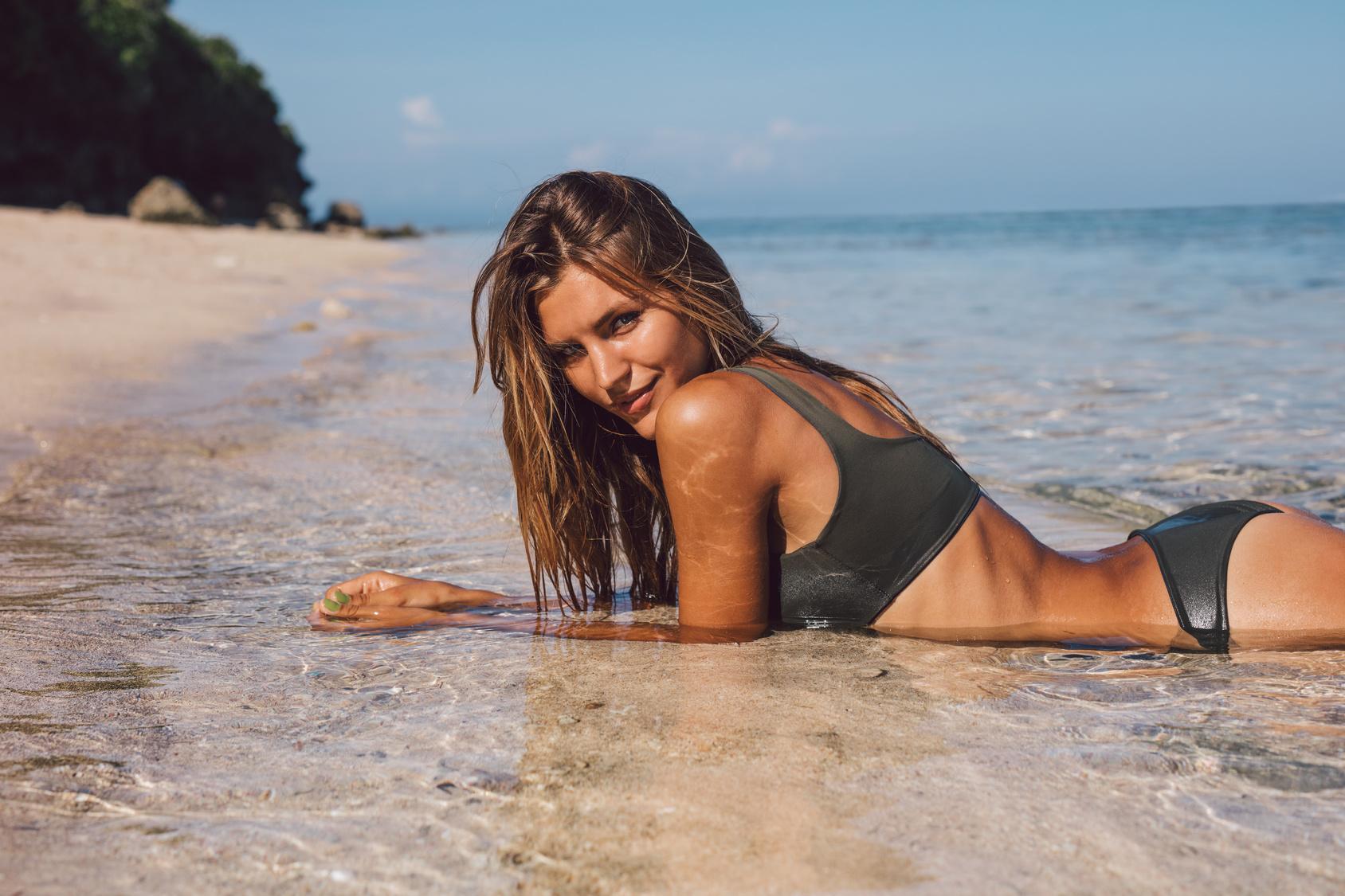 Shot of attractive young woman in bikini lying on the sea shore. Beautiful bikini model relaxing on the beach.