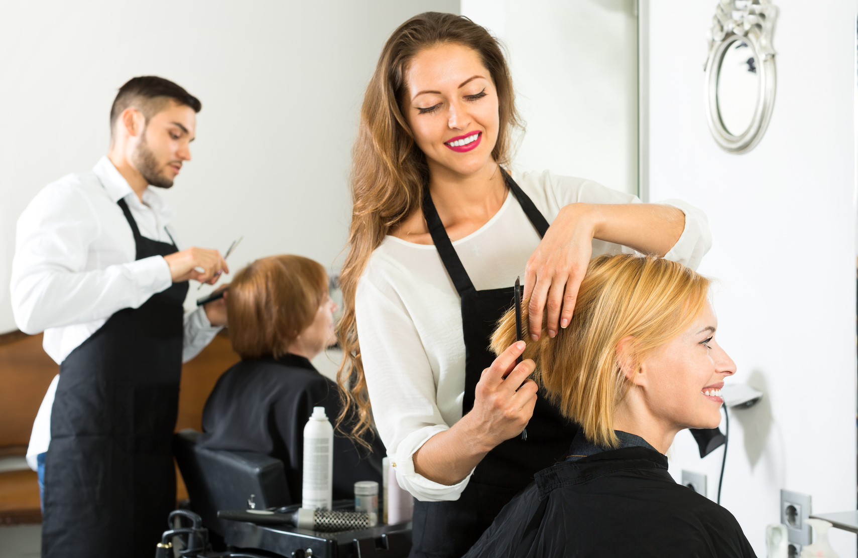 Smiling client sitting in a hair salon while hairdresser is combing her hair. Focus on client