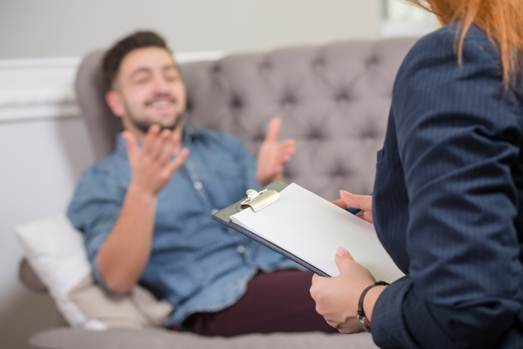 Close-up portrait of female psychiatrist making notes in front of patient during psychological therapy session.