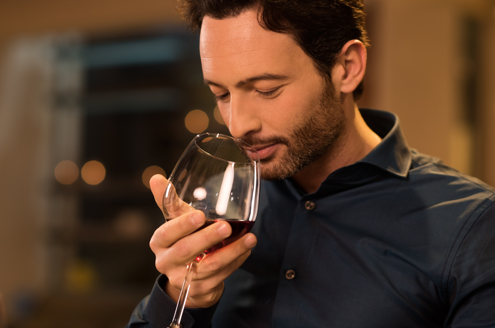 Handsome young man smelling red wine before drinking it. Young man drinking red wine in a luxury restaurant. Handsome young man tasting a glass of red wine during dinner.